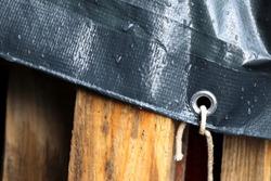 Plastic cloth with water drops. Waterproof surface. Woody palette under grey tarpaulin.