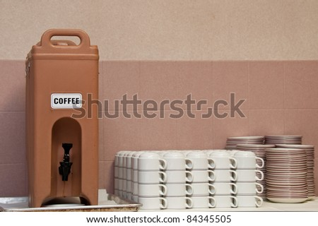 Plastic coffee dispenser sitting on a dirty drip pan. White coffee mugs and snack plates are also shown.