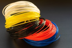 Plastic coils red (orange), white, yellow, blue on black background. Plastic PLA and ABS filament material for printing on a 3D pen