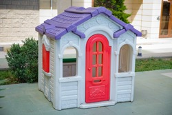 plastic colorful house . Entertainment area.kids playhouse in the entertainment center. Plastic children play house . Green floor. Joy and fun. Playing games.with red door and red window .Game house .