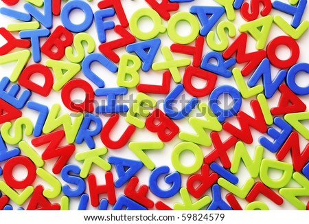 Plastic colorful random letters on white background. - stock photo