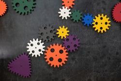 Plastic constructor gearwheels on dark wooden background. Popular toys. Copyspace