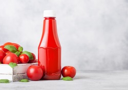 Plastic container with tomato ketchup sauce with raw tomatoes on kitchen background.