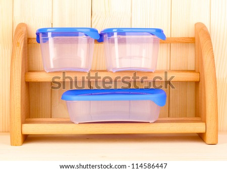 Plastic containers for food on shelf on wooden background