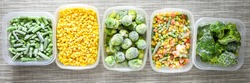 Plastic containers with frozen vegetables on grey background, top view, Different frozen vegetables on table, trendy food, corn brussels sprouts mixed green beans. Stocking up vegetables for winter