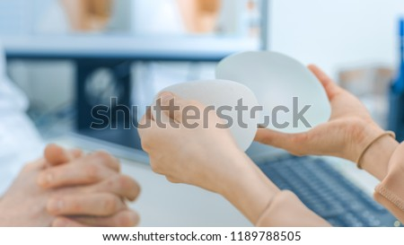 Plastic / Cosmetic Surgeon Shows Female Patient Breast Implant Samples for Her Future Surgery. Professional and Famous Surgeon Working in Respectable Clinic.