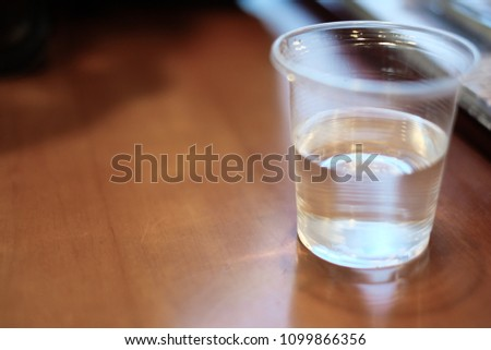Plastic cup. Put on clean drinking water. Half a glass of water.On the wood table.Water is the main ingredient in the human body. concept:Thirsty ,beverage