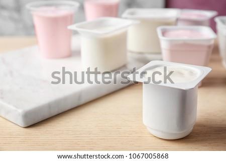 Plastic cup with tasty yogurt on table