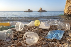 Plastic debris and face masks on the beach in surf zone. Coronavirus COVID-19 is contributing to pollution, as discarded used masks clutter polluting beaches of the Red Sea along with plastic trash