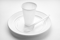 Plastic dishware. White vase, plate and fork on white background. Disposable plastic waste
