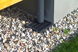 Plastic downspout, grill and pebble around a house, outdoor close up