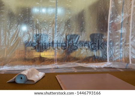 Plastic drop cloth hangs from ceiling to carpet floor to protect furniture from spills, paint drips and splatter, dust management, and debris during painting, demolishing or construction