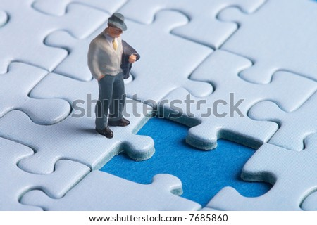 plastic figure standing in front of a hole in a puzzle - looks like big problems - there is one missing part