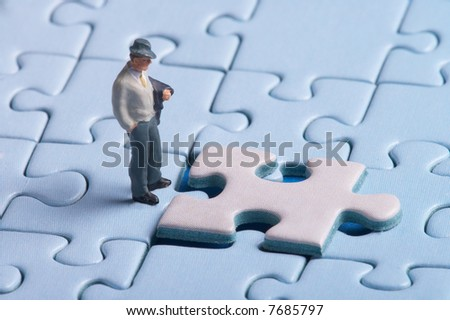 Plastic figure standing in front of a puzzle piece, a man (figure) has to make decisions, whether this is the right solution