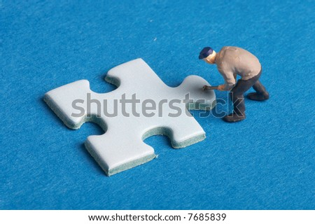 plastic figure with a puzzle piece on blue background - Plastikfigur mit einem Puzzleteil auf blauem Hintergrund