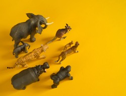 Plastic figurines of animals in hot countries. Protection of the animal. Children's toy. Yellow background.