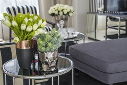 plastic flowers in pink flower vase on the rattan weave table decorated interior in living room