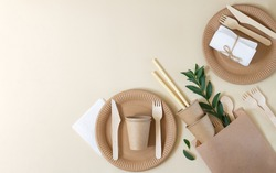 Plastic free and zero waste concept. Disposable paper tableware (cups, plates, wooden forks, knives, spoons and bamboo straws) on beige background top view