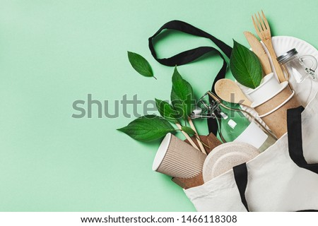 Plastic free set with cotton bag, glass jar, green leaves and recycled tableware top view. Zero waste, eco friendly concept. Flat lay.