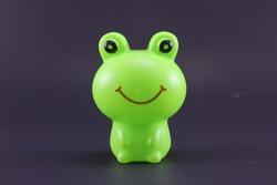 Plastic frog on black background