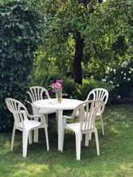 Plastic furniture set from nineties in super green garden environment. White chair and table and wild flowers in the glass. Vintage feeling