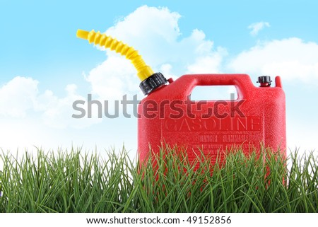Plastic gas can in grass against white background