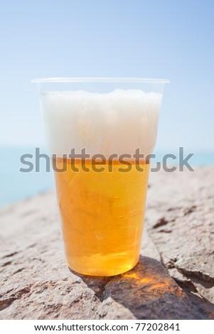 Plastic glass of beer on rock