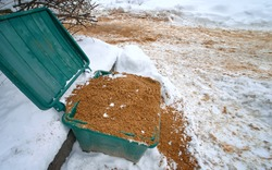 Plastic grit and salt bin mixture ready for winter. Open sand container close up. Plastic container with gritting material for slippery surface. Grit and salt bin, street furniture on the roadside