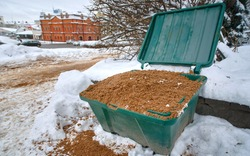 Plastic grit and salt bin ready for winter. Open sand container close up. Plastic container with gritting material for slippery surface. Grit and salt cuft, street furniture. Road treated with sand