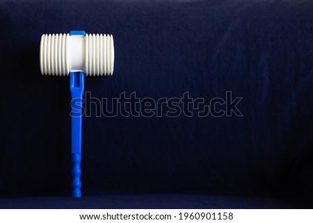 Plastic hammer in blue background. A tradition of the night of Saint John in Portugal. (Martelinho de S. João) Foto stock ©