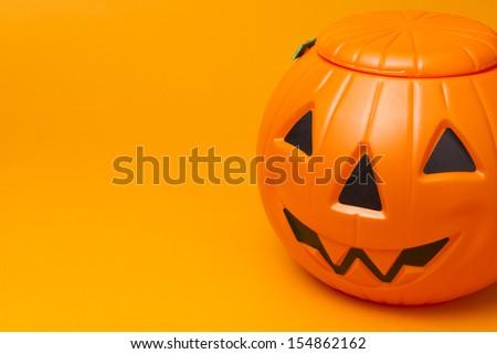 plastic jack-o-lantern on orange  background