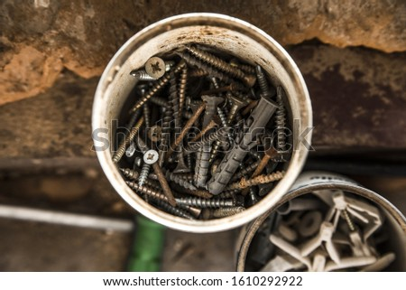 Plastic jar with self-tapping screws, bolts, screws, dowels and other equipment for repair.