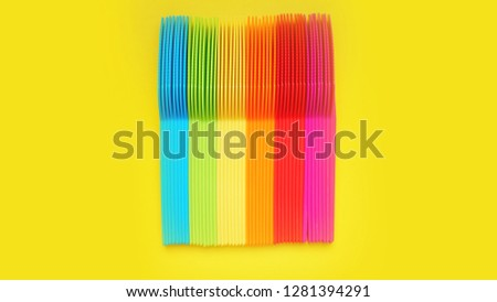 Plastic knives violet, orange, yellow, blue, red isolated on yellow background - bright summer concept for design and banners