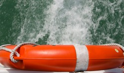 plastic life preserver of a boat seen from above with background water, orange life preserver