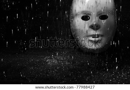 Plastic mask under the rain on a dark background