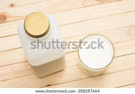 plastic milk bottle and milk in glass on pine wood plank