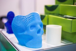 Plastic model of abstract blue human skull at modern technology exhibition. 3D printing, additive technologies and futuristic concept