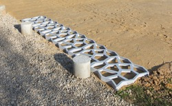 plastic molds for pouring concrete paths lie in a row on yellow sand, photo was taken on a sunny summer day