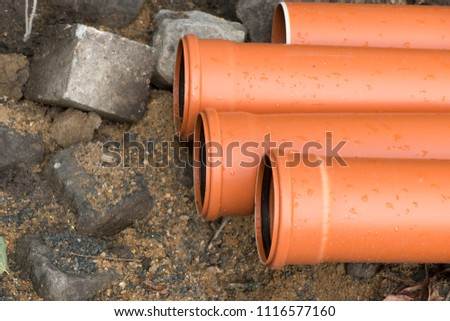 plastic orange pipes for drainage and sewerage during construction work #1116577160