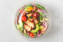 Plastic package with healthy chicken salad with avocado , tomatoes and pomegranate to take away. top view