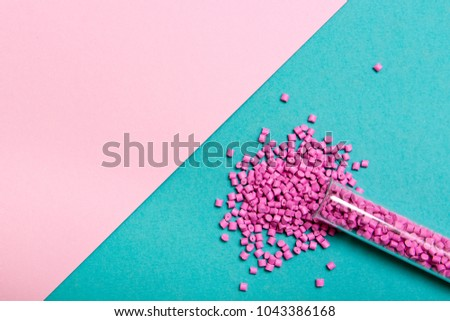 Plastic pallets . Plastic raw materials in granules for industry. Polymeric dye pink on a turquoise background. Plastic granules after processing of waste polyethylene and polypropylene.Polymer