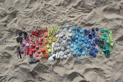 Plastic parts, found at the beach are arranged by color. Laydown in the sand.