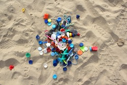 Plastic parts, found at the beach are collected and placed on the sand.