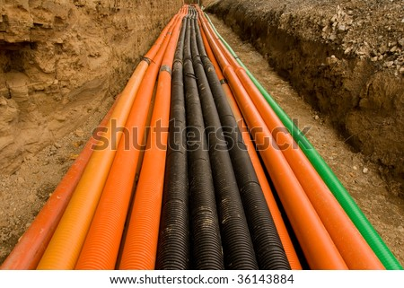 Plastic pipes containing electric cables, in a ditch ready to be filled