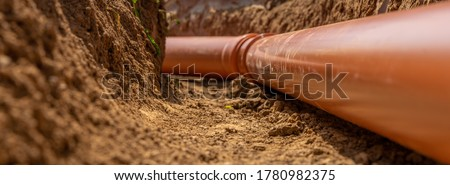 Plastic pipes in the ground during the construction of a building, bunner with copy space Foto stock ©