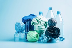 Plastic recycling and reuse concept. Empty plastic bottle and various fabrics made of recycled polyester fiber synthetic fabric on a blue background. Environmental protection waste recycling.