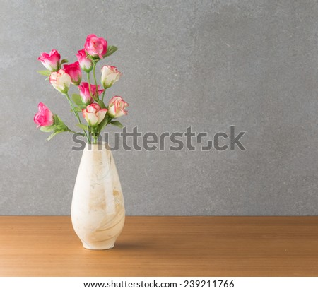 plastic rose in vase on wood table
