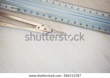plastic ruler and metal compass on a bright pastel wood background