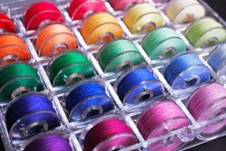 Plastic sewing machine bobbins with colorful threads in storage box