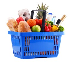 Plastic shopping basket with assorted gorcery products isolated on white